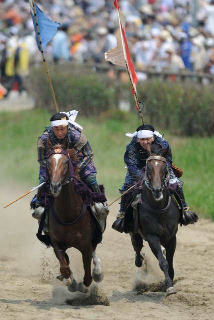 """Local people in samurai armor race horses during the annual Soma Nomaoi Festival in Minamisoma, Fukushima Prefecture, on July 29, 2012. Some 400 horses and thousands of people took part in the 1,000-year-old """"Soma Nomaoi"""", or wild horse chase, at the weekend in the shadow of Japan's crippled Fukushima nuclear plant. (Photo by Toru Yamanaka/AFP Photo)"""