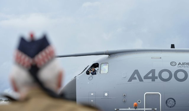A crew member onboard an Airbus A400M signals to plane enthusiasts on the ground during the Farnborough International Airshow in Farnborough, Britain, 12 July 2016. (Photo by Hannah Mckay/EPA)
