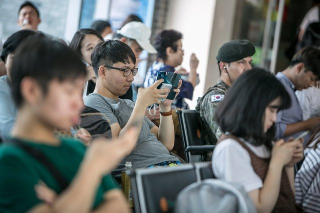 South Korean youths play Pokemon Go at the Express Bus Terminal on July 15, 2016 in Sokcho, South Korea. (Photo by Jean Chung/Getty Images)