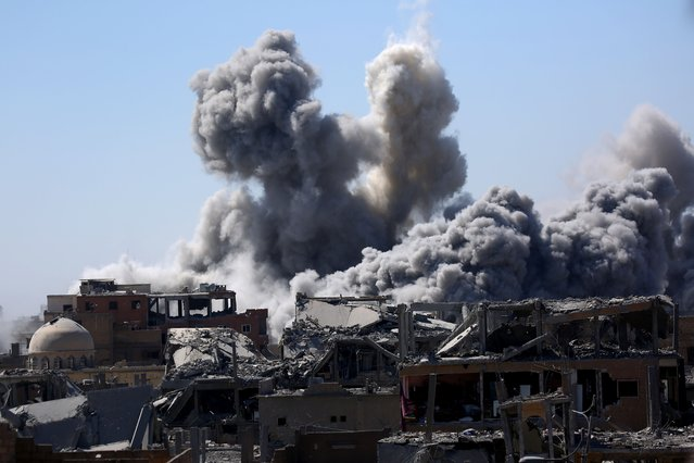 Smoke billows in the embattled northern Syrian city of Raqa on September 3, 2017, as Syrian Democratic Forces (SDF), a US backed Kurdish-Arab alliance, battle to retake the city from the Islamic State (IS) group. (Photo by Delil Souleiman/AFP Photo)