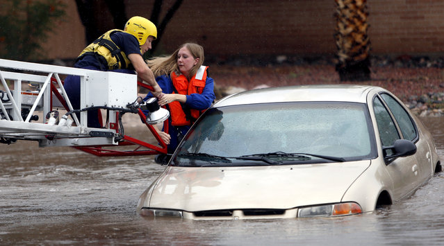 Tucson Fire Department personnel use a ladder truck to rescue a woman from a car stranded in rising flood waters in east Tucson, Ariz., Tuesday, August 19, 2014. (Photo by Kelly Presnell/AP Photo/Arizona Daily Star)