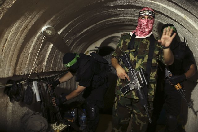 A Palestinian fighter from the Izz el-Deen al-Qassam Brigades, the armed wing of the Hamas movement, gestures inside an underground tunnel in Gaza August 18, 2014. A rare tour that Hamas granted to a Reuters reporter, photographer and cameraman appeared to be an attempt to dispute Israel's claim that it had demolished all of the Islamist group's border infiltration tunnels in the Gaza war. (Photo by Mohammed Salem/Reuters)