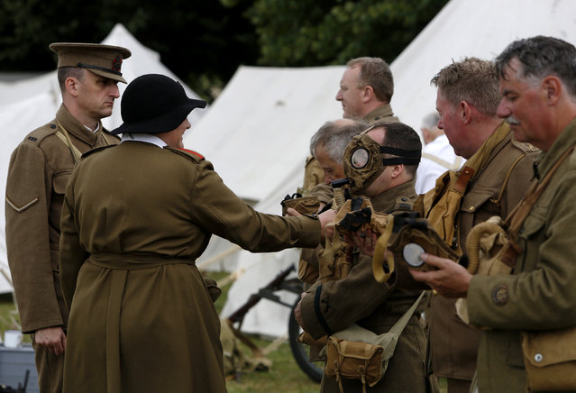 Senior construction manager Paul Barker (3rd R) portrays a Corporal in the Kings Royal Rifle Corps with the Rifles Living History Society as he participates in a gas mask check with Ciaran Watts (L), portraying a Lance Corporal, and Pat Taylor (2L) who is dressed as a member of the Women's Auxilliary Army Corps at the Colchester Military Tournament in Colchester, eastern England July 5, 2014. (Photo by Luke MacGregor/Reuters)
