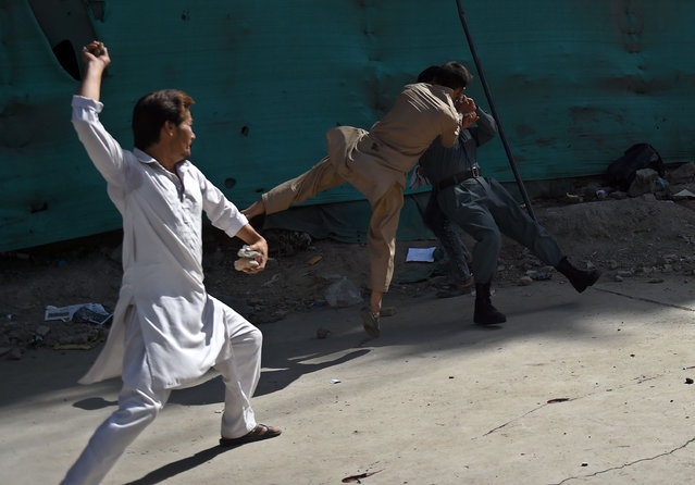 Afghan protesters beat a policeman after a suicide attack that targeted crowds of minority Shiite Hazaras during a demonstration at the Deh Mazang Circle of Kabul on July 23, 2016. Islamic State jihadists claimed responsibility for twin explosions July 23 that ripped through crowds of Shiite Hazaras in Kabul, killing at least 61 people and wounding 207 others in apparently their deadliest attack in the Afghan capital. The bombings during a huge protest over a power transmission line could deepen sectarian divisions in a country well known for communal harmony despite decades of war. (Photo by Wakil Kohsar/AFP Photo)