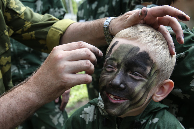 A group leader paints a boy's face in preparation for a military sports game at a children's camp in Moscow, Russia on July 29, 2016. (Photo by Vyacheslav Prokofyev/TASS)
