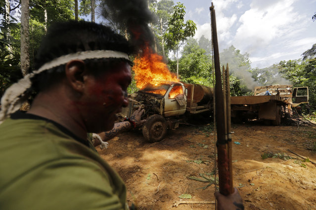 A Ka'apor Indian warrior stands near a logging truck they discovered and set on fire during a jungle expedition to search for and expel loggers from the Alto Turiacu Indian territory, near the Centro do Guilherme municipality in the northeast of Maranhao state in the Amazon basin, August 7, 2014. (Photo by Lunae Parracho/Reuters)