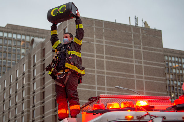 "A member of the New York City Fire Department stands on top of a firetruck holding up a speaker playing ""New York, New York"" by Frank Sinatra in honor of medical staff and essential workers outside of NYU Langone Health hospital amid the coronavirus pandemic on April 30, 2020 in New York City, United States. COVID-19 has spread to most countries around the world, claiming over 230,000 lives with over 3.2 million cases. (Photo by Alexi Rosenfeld/Getty Images)"