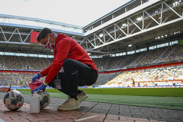 Footballs are disinfected during the Bundesliga soccer match between Duesseldorf and Paderborn in the Merkur Spiel-Arena, Duesseldorf, Germany, Saturday, May 16, 2020. The German Bundesliga becomes the world's first major soccer league to resume after a two-month suspension because of the coronavirus pandemic. (Photo by Sascha Schuermann/AFP pool via AP Photo)