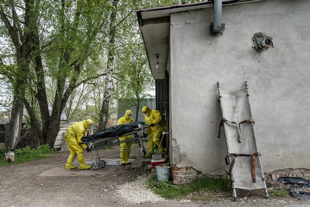 In this photo taken on Thursday, April 30, 2020, pathologists wearing special suits to protect against coronavirus, transport the body of a man who died of coronavirus, at the doors of the morgue in Ternopil, Ukraine. (Photo by Evgeniy Maloletka/AP Photo)