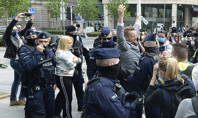Police, wearing face masks to protect against coronavirus, detain independent candidate in Poland's presidential election, Pawel Tanajno, center, during a small protest of business people opposing coronavirus lockdown measures, in Warsaw, Poland, Saturday, May 23, 2020. (Photo by Czarek Sokolowski/AP Photo)