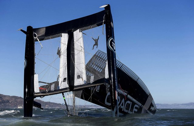 Crew members hang from mesh netting after the Oracle Team USA AC72 boat capsized in San Francisco Bay. The America's Cup champion syndicate is assessing the damage to its 72-foot catamaran after it capsized and was swept by a strong current more than four miles past the Golden Gate Bridge before rescue boats could control it. (Photo by Guilain Grenier/Oracle Team USA)