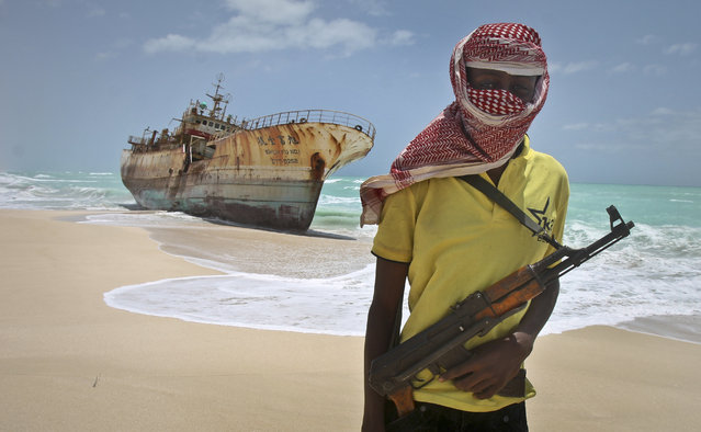 In this Sunday, September 23, 2012 file photo, masked Somali pirate Hassan stands near a Taiwanese fishing vessel that washed up on shore after the pirates were paid a ransom and released the crew, in the once-bustling pirate den of Hobyo, Somalia. (Photo by Farah Abdi Warsameh/AP Photo)
