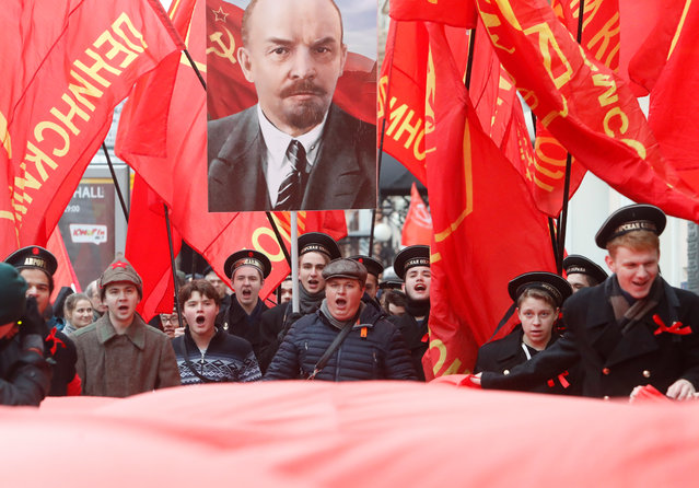 Demonstrators carry flags and a portrait of Soviet state founder Vladimir Lenin during a rally held by Russian Communist party to mark the Red October revolution's centenary in central Moscow, Russia on November 7, 2017. (Photo by Sergei Karpukhin/Reuters)