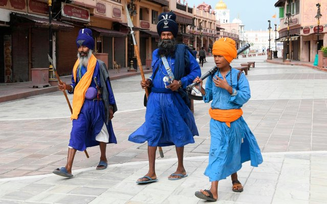 Sikh Nihang's Singh (Sikh warriors) walk along the empty Heritage Street after strict lockdown norms for weekends and public holidays were imposed as a preventive measure against the COVID-19 coronavirus, in Amritsar on June 13, 2020. (Photo by Narinder Nanu/AFP Photo)