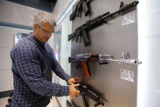A man browses a model of the Vityaz submachine gun at the newly opened Gunmaker Kalashnikov souvenir store in Moscow's Sheremetyevo airport, Russia, August 22, 2016. (Photo by Maxim Shemetov/Reuters)