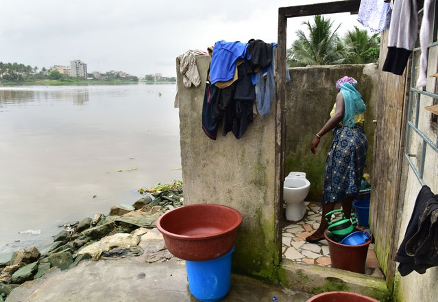 A woman cleans a toilet in an impoverished neighbourhood near a lagoon in Abidjan, Ivory Coast on November 14, 2017. (Photo by Issouf Sanogo/AFP Photo)