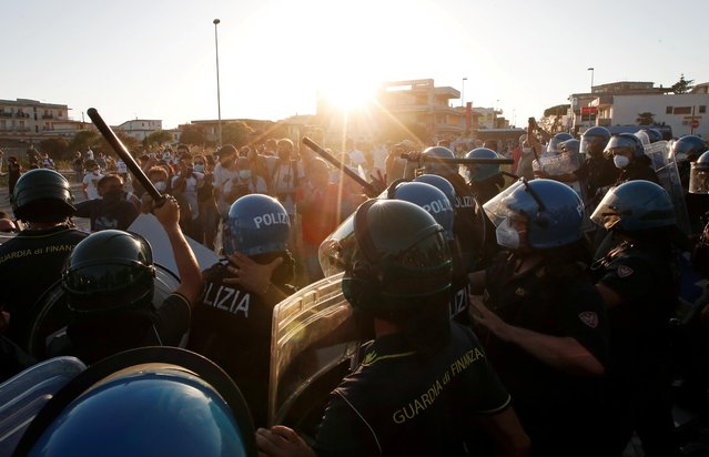 Police clash with protestors during a visit of Italy's far-right League party leader Matteo Salvini at a village near Naples, after more than 40 people tested positive for the coronavirus disease (COVID-19) in a residential complex, in Mondragone, Italy, June 29, 2020. (Photo by Ciro de Luca/Reuters)