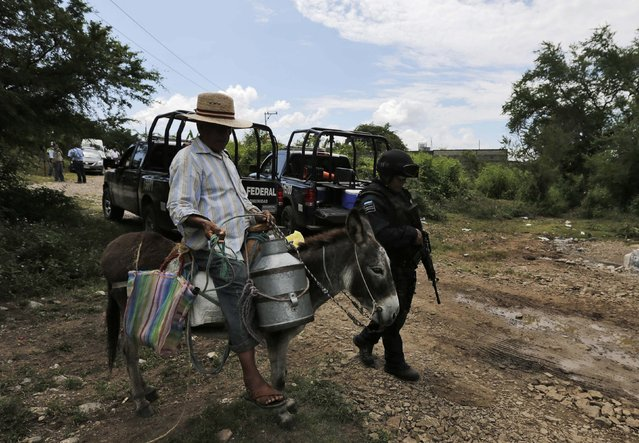 A resident rides a donkey past a federal police officer on a road at an area near clandestine graves at Pueblo Viejo, in the outskirts of Iguala, southern Mexican state of Guerrero October 10, 2014. Mexican authorities have found four more clandestine graves containing charred human remains at a site in the restive southwest of the country, where officials fear missing students were massacred by gang members and police. (Photo by Henry Romero/Reuters)