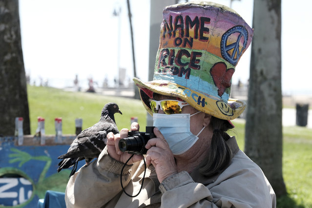 Vendor Vivianne Robinson, wearing a mask to protect from the coronavirus, takes a photo with a pigeon perched on her hand along the Venice Beach strand, Friday, July 3, 2020, in Los Angeles. California's governor is urging people to wear masks and skip Fourth of July family gatherings as the state's coronavirus tally rises. Newsom said he'd rely on people using common sense rather than strict enforcement of the face-covering order. (Photo by Richard Vogel/AP Photo)