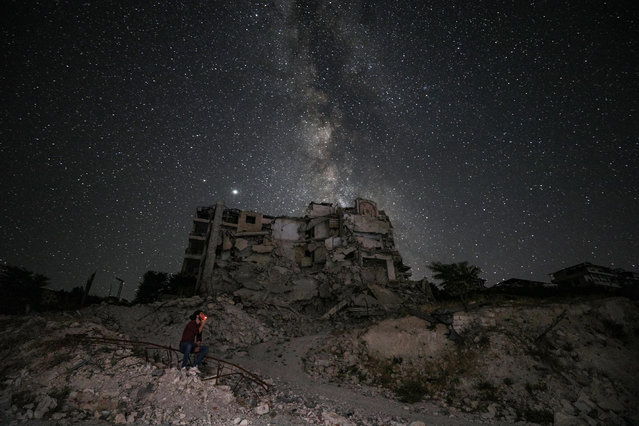 This long-exposure picture taken early on June 27, 2020 shows a man smoking past buildings destroyed by prior bombardment in the town of Ariha in Syria's rebel-held northwestern Idlib province, as the Milky Way galaxy is seen in the night sky above. (Photo by Omar Haj Kadour/AFP Photo)