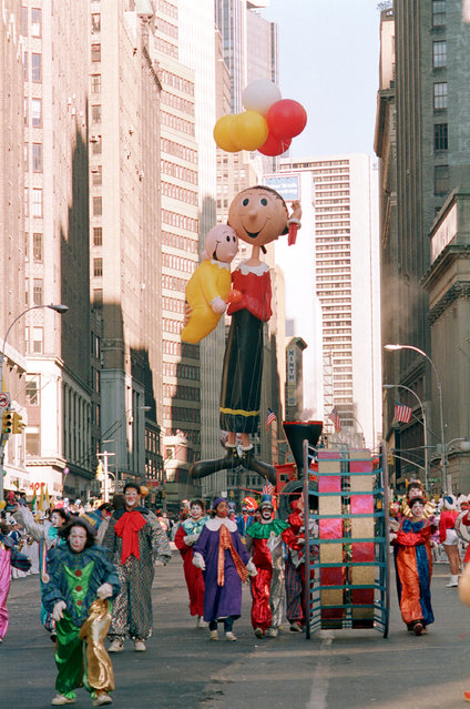 The redesigned balloon of Olive Oyl, holding Swee' Pea, floats behind a group of clowns as they march down Broadway in the annual Macy's Thanksgiving Day Parade in New York City, Thursday, November 27, 1986. (Photo by AP Photo)