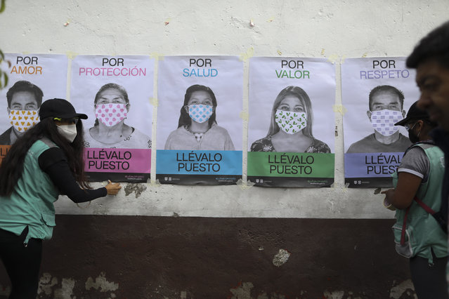 """A man not wearing a face mask walks by as city health department workers affix a series of posters advocating mask use to a wall, in San Mateo Xalpa in the Xochimilco district of Mexico City, Tuesday, July 21, 2020. The posters say, in Spanish, """"For love, for protection, for health, for self-worth, for respect, wear it"""". To help battle the pandemic in hard-hit areas, the city health department has set up mobile testing units and sent teams of workers to hang posters and distribute informational pamphlets about how to prevent tCOVID-19. (Photo by Rebecca Blackwell/AP Photo)"""