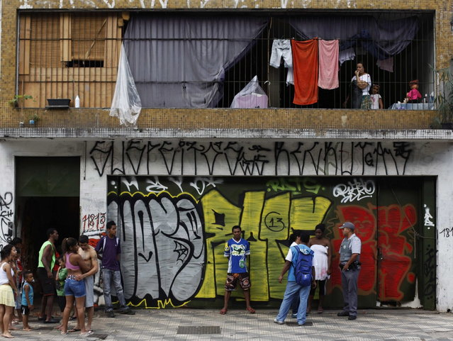 A leader (2nd R, white smock) of Brazil's Movimento dos Sem-Teto (Roofless Movement) speaks to a state health worker (in blue) and a policeman, outside one of the 11 empty buildings that the movement took over recently, in the centre of Sao Paulo, December 4, 2012. According to City Hall, there are some 400,000 people in need of stable housing, including the 4,000 families of the Roofless Movement who are squatting in abandoned or vacant buildings that range from apartment blocks to hotels, in Sao Paulo, the largest city in South America. (Photo by Nacho Doce/Reuters)