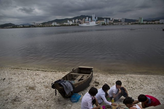 In this June 21, 2014 photo, a group of young North Koreans enjoys a picnic on the beach in Wonsan, North Korea. (Photo by David Guttenfelder/AP Photo)
