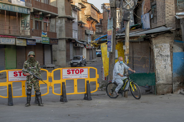 A Kashmiri cycles past a barricade set up as road blockade as a paramilitary soldier stands guard on the first anniversary of India's decision to revoke the disputed region's semi-autonomy, in Srinagar, Indian controlled Kashmir, Wednesday, August 5, 2020. Last year on Aug. 5, India's Hindu-nationalist-led government of Prime Minister Narendra Modi stripped Jammu-Kashmir of its statehood and divided it into two federally governed territories. Late Tuesday, authorities lifted a curfew in Srinagar but said restrictions on public movement, transport and commercial activities would continue because of the coronavirus pandemic. (Photo by Dar Yasin/AP Photo)