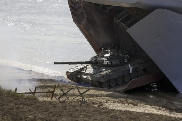 A tank rolls out from a ship on a landing operation during military drills at the Black Sea coast, Crimea, Friday, September 9, 2016. (Photo by Pavel Golovkin/AP Photo)