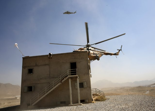 An Afghan National Army (ANA) helicopter approaches a building during a training exercise at the Kabul Military Training Centre in Afghanistan October 7, 2015. (Photo by Ahmad Masood/Reuters)
