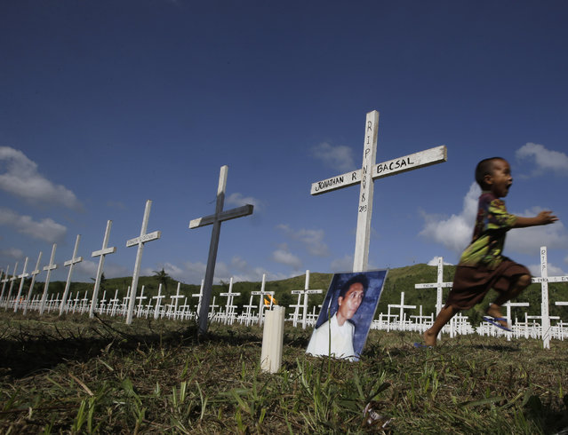 Typhoon survivor Jonathan Bacsal Jr., runs past a cross that indicates his father Jonathan Bacsal Sr. is buried at a mass grave for typhoon Haiyan victims in the outskirts of Tacloban city, Leyte province in central Philippines Thursday, November 6, 2014. His father perished after being hit by a flying piece of tin roof while trying to herd them to safety as the horrific Nov. 8, 2013 storm leveled entire villages in Tacloban city on Leyte island. (Photo by Bullit Marquez/AP Photo)