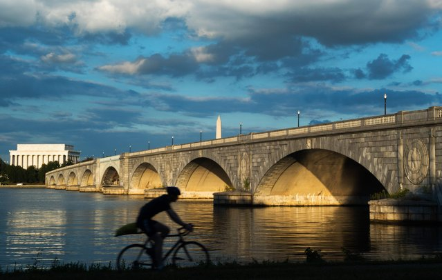 A bicyclist rides during sunset along the Mt. Vernon Trail that follows the Potomac River in Virginia near the Arlington Memorial Bridge, the Lincoln Memorial and Washington Monument seen in the background, September 15, 2017, in Washington, DC. (Photo by Paul J. Richards/AFP Photo)