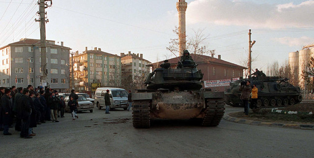 A Turkish tank is followed by an armoured vehicle as around 20 tanks and armoured carriers parade through the streets of the Sincan district, near the capital Ankara, Turkey, in this file photo taken on February 4, 1997. (Photo by Reuters/File photo)