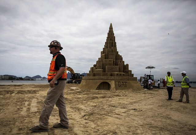 A group of people gather next to a giant sand castle at Niteroi, Rio de Janeiro, Brazil, 11 November 2014. A tractor's maker company seeks to be included in the Guinness records building the world's largest sand castle, beating the last holder of the title, which was 11.63 meters high. (Photo by Antonio Lacerda/EPA)