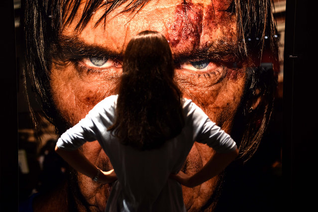 "A visitor stands in front of a portrait taken by artist Bruce Gilden at the ""Masters of Photography"" exhibition at the Photokina trade fair in Cologne on September 20, 2016. The fair for the photographic and imaging sector, that is running from September 20 to 25, 2016, presents products from image capture, image processing and storage to image output. Photokina also includes a program of events with congresses, workshops, symposiums and photography exhibitions. (Photo by Patrik Stollarz/AFP Photo)"