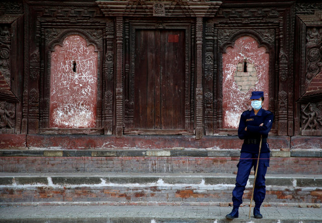 A police personnel stands guard near the polling station at Hanumandhoka Durbar Square, a day ahead of the parliamentary and provincial elections in Kathmandu, Nepal on December 6, 2017. (Photo by Navesh Chitrakar/Reuters)