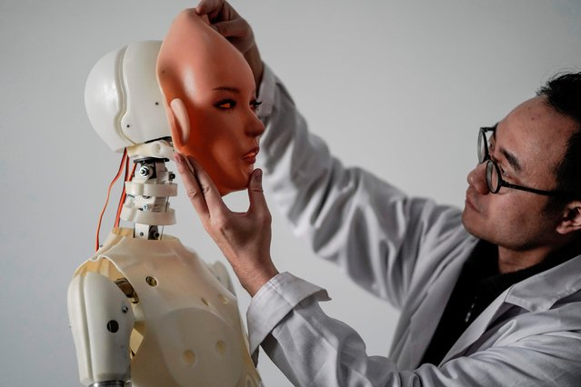 This photo taken on February 1, 2018 shows an engineer holding a silicon face against the head of a robot at a lab of a doll factory of EXDOLL, a firm based in the northeastern Chinese port city of Dalian. (Photo by Fred Dufour/AFP Photo)