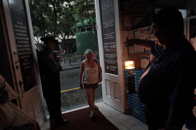 A client enters a drugstore during a power outage after a fire at an energy plant knocked out electricity for the bulk of the island, in San Juan, Puerto Rico, September 22, 2016. (Photo by Alvin Baez/Reuters)