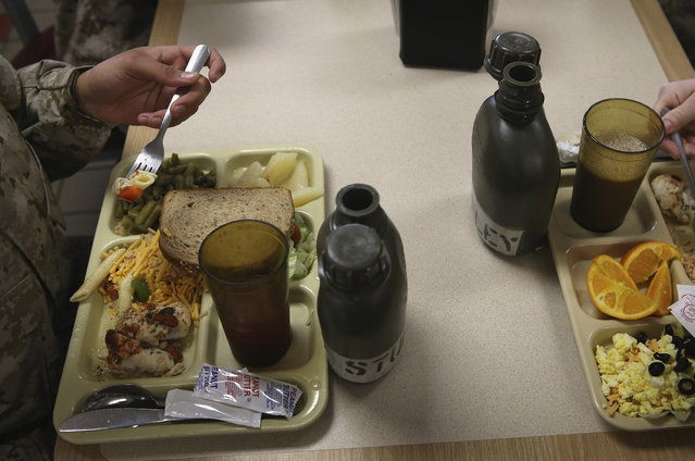 As mandated by their drill instructors, female Marine recruits place their water canteens directly in front of their beverage glass while having lunch during boot camp on February 26, 2013 at MCRD Parris Island, South Carolina. Female enlisted Marines have gone through recruit training at the base since 1949. About 11 percent of female recruits who arrive at the boot camp fail to complete the training, which can be physically and mentally demanding. On January 24, 2013 Secretary of Defense Leon Panetta rescinded an order, which had been in place since 1994, that restricted women from being attached to ground combat units. (Photo by Scott Olson/AFP Photo)