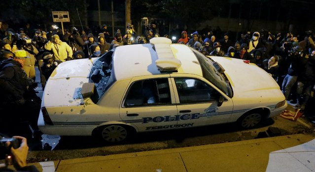 Protesters vandalize a police vehicle outside of the Ferguson city hall on Tuesday, November 25, 2014, in Ferguson, Mo. (Photo by Charlie Riedel/AP Photo)