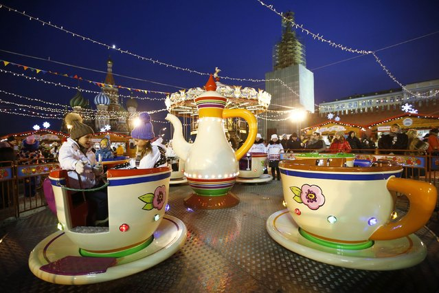 Children sit in a teacups ride on the first day of a fair organized by GUM departmental store for the upcoming Christmas and New Year celebrations at Moscow's Red Square, November 29, 2014. (Photo by Maxim Zmeyev/Reuters)