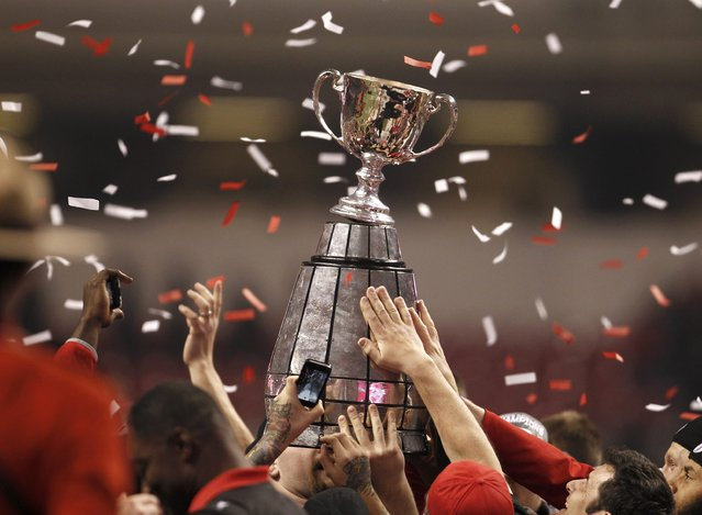 Calgary Stampeders players hold up a broken Grey Cup as they celebrate defeating the Hamilton Tiger Cats in the CFL's 102nd Grey Cup football championship in Vancouver, British Columbia, November 30, 2014. (Photo by Andy Clark/Reuters)