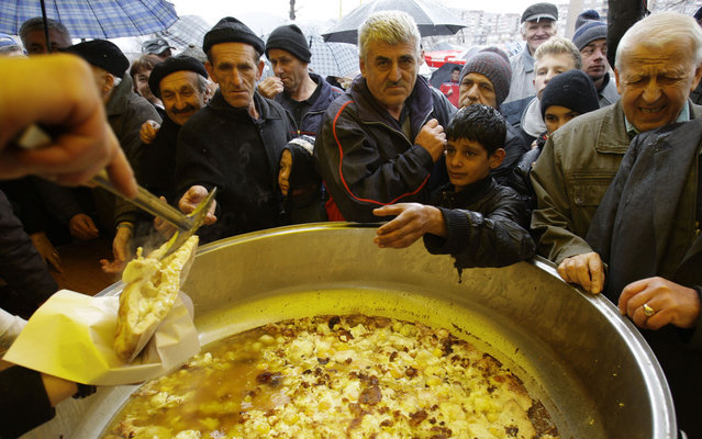 """Scrambled eggs are served during the """"Cimburijada"""" or festival of scrambled eggs, in a park of Zenica, Bosnia, on March 21, 2013. Every year, city residents gather at the site to celebrate the arrival of spring. (Photo by Amel Emric/AP Photo)"""