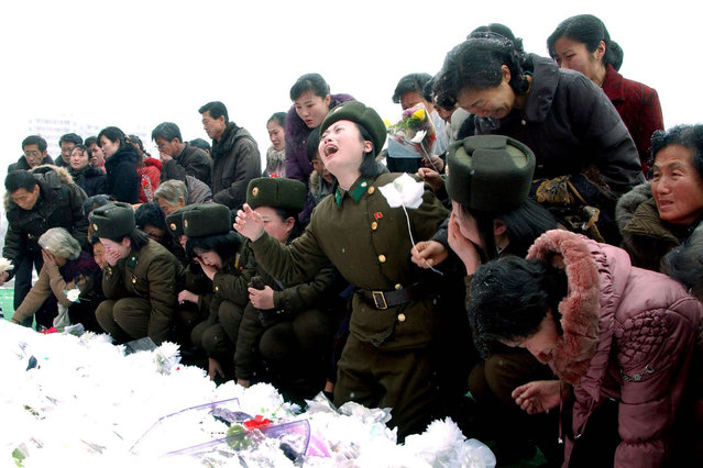North Koreans react as they make a call of condolence for deceased leader Kim Jong Il in Pyongyang, on December 21, 2011. (Photo by Reuters/KCNA)