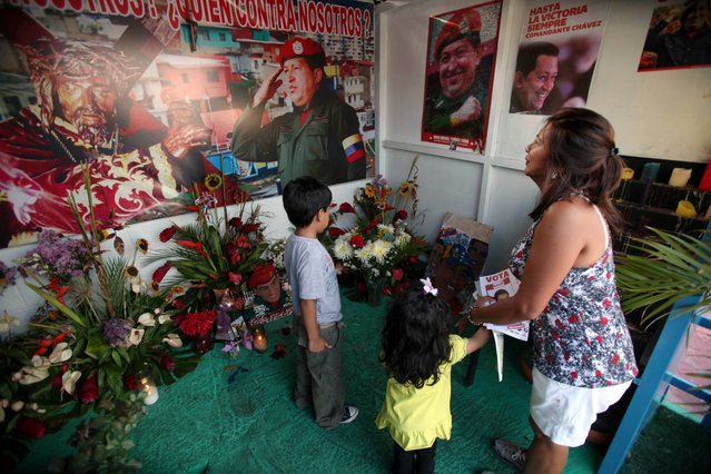 """A woman and her two children visit a people's shrine built in honor of late Venezuela's President Hugo Chavez at the """"23 de Enero"""" or """"23rd of January"""" slum in Caracas, Venezuela, Wednesday, April 3, 2013. The shrine, named  """"Saint Hugo Chavez del 23"""", has been visited by tens of thousands of Venezuelans to pay homage to a president for some, a saint for others. (Photo by Fernando Llano/AP Photo)"""