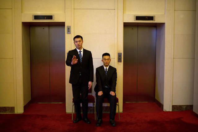 In this Tuesday, March 6, 2018 photo, security officials gesture as they stand guard at a bank of elevators at the Great Hall of the People in Beijing. (Photo by Mark Schiefelbein/AP Photo)