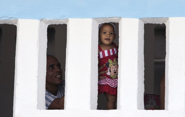 A prisoner holds up a young visitor toward the press during visiting hours a the Combinado del Este prison during a media tour of the prison in Havana, Cuba, Tuesday, April 9, 2013. Cuban authorities led foreign journalists through the maximum security prison, the largest in the Caribbean country that houses 3,000 prisoners. Cuba says they have 200 prisons across the country, including five that are maximum security. (Photo by Franklin Reyes/AP Photo)