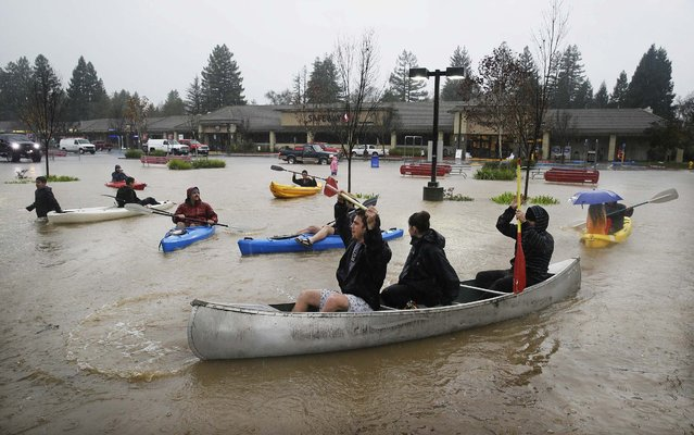 People use kayaks and a canoe to make their way around a flooded parking lot at a shopping center Thursday, December 11, 2014, in Healdsburg, Calif. A powerful storm churned through Northern California Thursday, knocking out power to tens of thousands and delaying commuters while soaking the region with much-needed rain. (Photo by Eric Risberg/AP Photo)