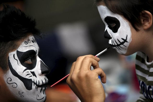 "A man with his face painted to look like the popular Mexican figure called ""Catrin "", paints a boy's face as they take part in the annual Catrina Fest in Mexico City November 1, 2015. (Photo by Carlos Jasso/Reuters)"